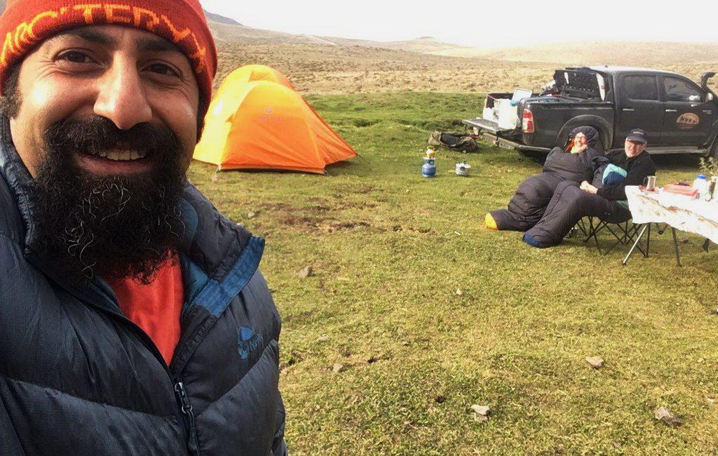Iran: Camping am Kuh-e Sabalan im Frühsommer. Die Reisenden sitzen warm eingepackt beim Frühstück