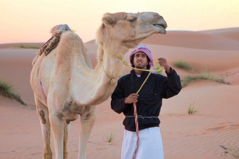 Oman: junger Mann mit Kamel in der Wahiba (copyright Bea Müller)